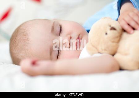 Schlafendes Baby Kind im Bett, ein Teddybär. - Stockfoto