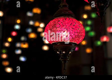 Marokkanische Laternen, beleuchtet und von der Decke in sortierten Farben gegen einen dunklen Hintergrund ausgesetzt - Stockfoto