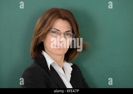 Porträt der jungen Lehrerin gegen grüne Tafel - Stockfoto