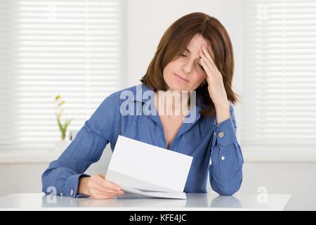 Traurige junge Frau liest Dokument in Office - Stockfoto