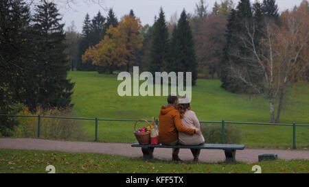 Liebe Paar auf der Werkbank. junges Paar sitzt auf der Bank im Park. Rückansicht. ein Paar auf einer Bank sitzen, - Stockfoto