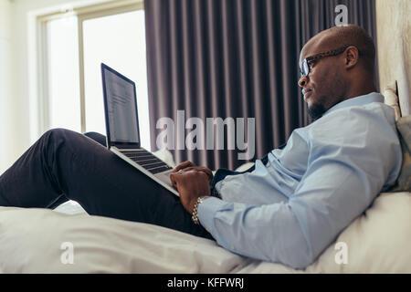 Mann in formelle Kleidung Arbeiten am Laptop im Bett lag. Unternehmer Arbeiten am Laptop aus seinem Hotelzimmer. - Stockfoto