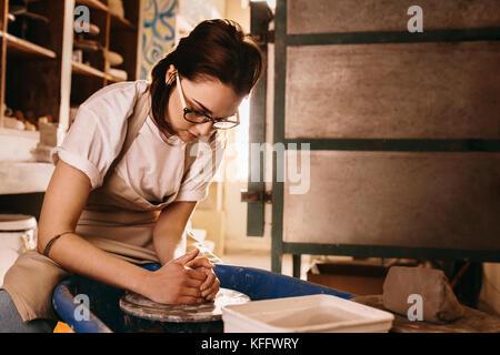 Frau molding Clay auf Keramik Rad. Handwerkerin, Topf in der Werkstatt. - Stockfoto
