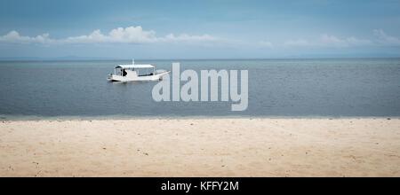 Ein einzelnes Boot im Wasser auf eine ruhige See auf der philippinischen Insel Malapascua - Stockfoto