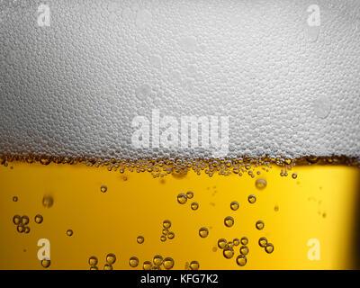 Nahaufnahme des frisch gezapften gold Bernstein Bier mit schaumigen Kopf und Kohlensäure blasen - Stockfoto
