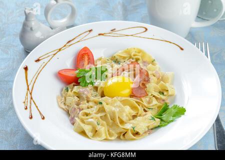 Spaghetti mit Schinken und Käse, serviert auf weiße Platte - Stockfoto
