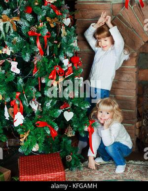 Zwei glückliche kleine Schwestern zu Hause mit Weihnachtsbaum und Geschenke - Stockfoto