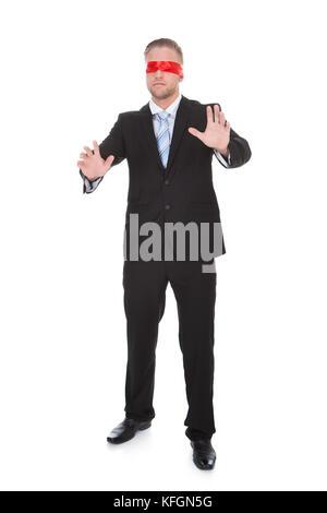 Stilvolle Junge Unternehmer trägt eine rote Binde seine Hände ausstreckte vor ihm für unsichtbare Hindernisse in - Stockfoto
