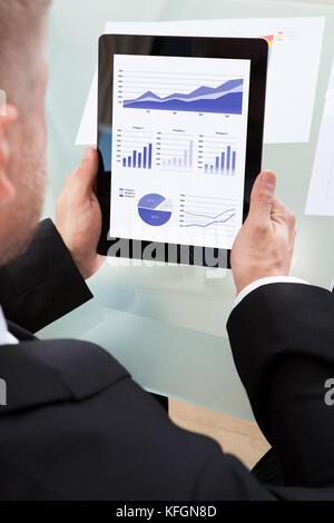 Geschäftsmann mit einer Reihe von Diagrammen auf seinem Tablet Computer suchen, als er an seinem Schreibtisch über - Stockfoto