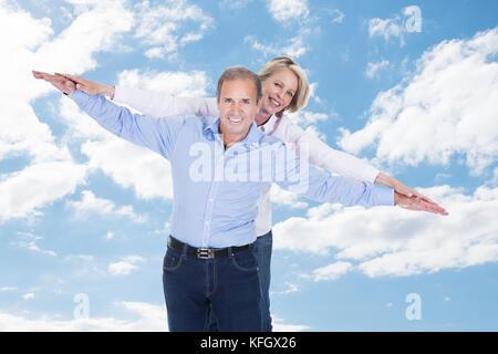 Portrait von glücklichen Paar mit ausgestreckten Armen stehend gegen bewölkter Himmel - Stockfoto