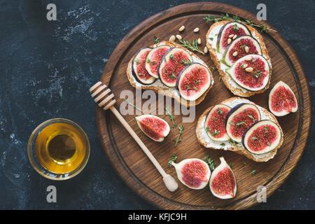 Frische Feigen- und Ziegenkäse Bruschetta mit Pinienkernen, Honig und Thymian gekrönt. Gourmet Vorspeise, gesunde - Stockfoto