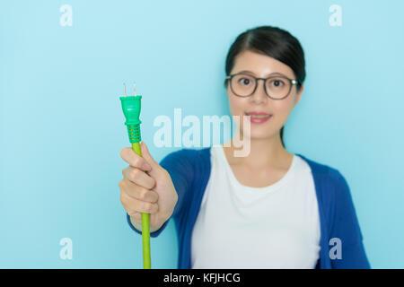 Selektiver Fokus Foto der lächelnden Schönheit Frau in Blau Hintergrund holding Plug Linie, elektrische Konzept - Stockfoto