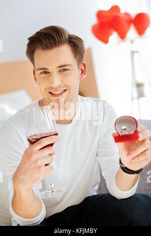 Glückliche junge Mann mit Verlobungsring, Wein trinken und - Stockfoto