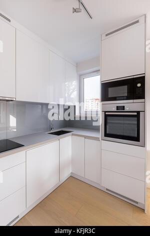 Funktionelle Küche mit grauen Schränke, Fenster und Waschbecken ...