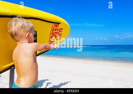Lebensrettende gelb Board mit surf Rescue unterzeichnen. lustig Kinder Rettungsschwimmer stehen, Blick auf Meer. Schwimmen Menschen Sicherheit. Familie Ferien Stockfoto