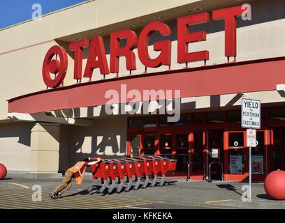 Eine junge Mitarbeiterin schieben Einkaufswagen in die Target Store in Bellingham, Washington. Der junge Mann hat - Stockfoto
