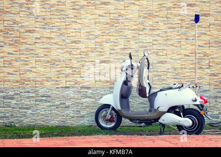 Batumi, Georgien - Oktober, 22, 2017: elektrische Motorroller in der Nähe von einem schönen Wand zum Laden geparkt. - Stockfoto