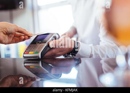Hand des Kunden bezahlen mit kontaktlosen Kreditkarte mit der NFC-Technologie. Bartender mit einem credit card reader - Stockfoto