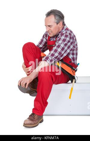 Männliche Techniker leiden unter Knieschmerzen auf weißem Hintergrund - Stockfoto