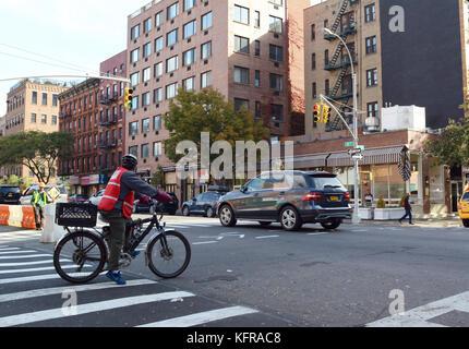 New York - 23. Oktober 2017: Lieferung Radfahrer trägt eine hohe Sichtbarkeit Waffenrock wartet an einer roten Ampel - Stockfoto