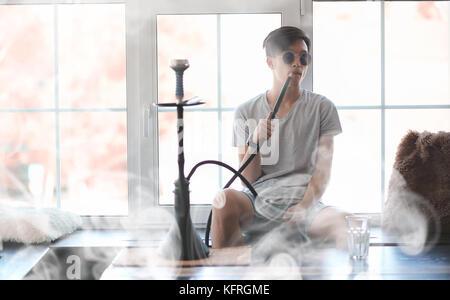 Mann in Sonnenbrille Rauchen einer Wasserpfeife - Stockfoto