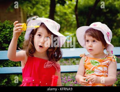 Zwei kleine Mädchen (Schwestern) Spaß und Seifenblasen. Sommerzeit - Stockfoto