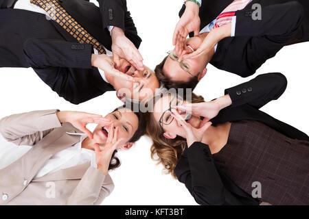 Konzeptionelle Bild von vier Geschäftsleute mit ihren Köpfen zusammen, die direkt auf die Kamera isoliert auf weißem - Stockfoto
