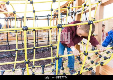 Kleiner Junge spielt auf gelbes Seil Brücke auf Jungle Gym - Stockfoto