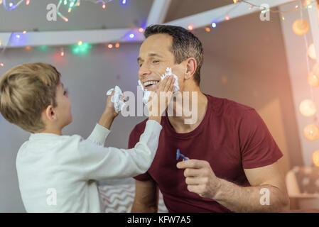 Lustig junge hilft seinem Vater zu rasieren - Stockfoto