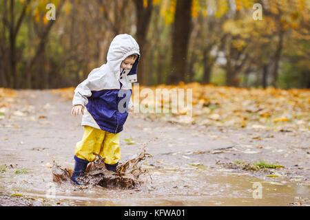 Gerne zwei Jahre alten Jungen springen auf schlammigen Pfützen in Gummistiefel - Stockfoto