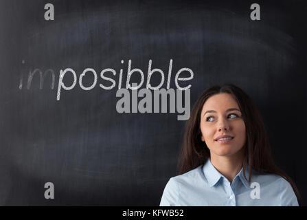 Business Frau Suchen Links und Denken das Wort unmöglich möglich. - Stockfoto