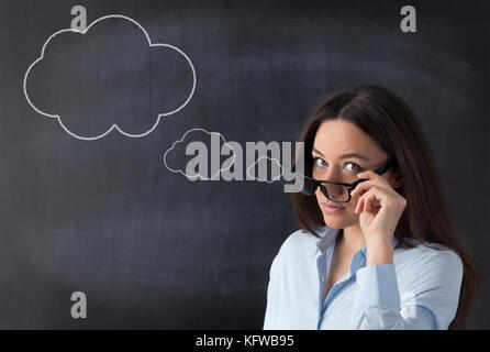 Sie hält ihre Brille mit der Hand direkt an der Kamera vor der Tafel auf der Suche - Stockfoto
