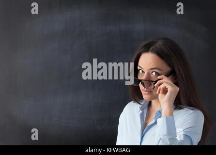 Sie hält ihre Brille mit der Hand und direkt auf die Kamera. - Stockfoto