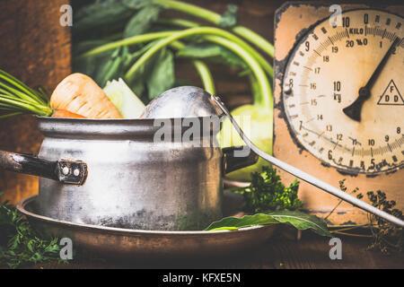 Alten Kochtopf mit rohem Gemüse und Kelle auf rustikale Küche Tabelle, Ansicht von vorne - Stockfoto