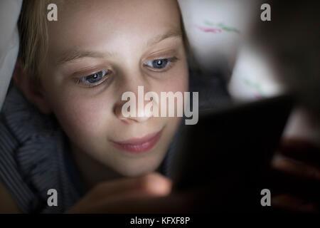 Mit Handy versteckt unter Bettdecke nachts im Bett Mädchen - Stockfoto