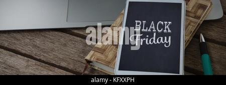 Laptop, Mobiltelefon, Milchprodukte und Stift auf Holzbrett gegen schwarze Freitag - Stockfoto