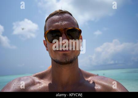 Mann mit kurzen Haaren, Bart und Sonnenbrille nimmt eine selfie am Strand - Stockfoto