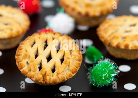 Frisch goldbraun Gitter oben mince pies gegen eine dekorierte Weihnachten Hintergrund - Stockfoto