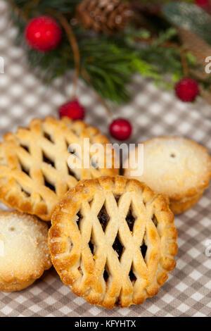 Frsh Gitter oben Mince Pies auf ein Land Tabelle mit einigen festlichen saisonale Weihnachtsschmuck - Stockfoto