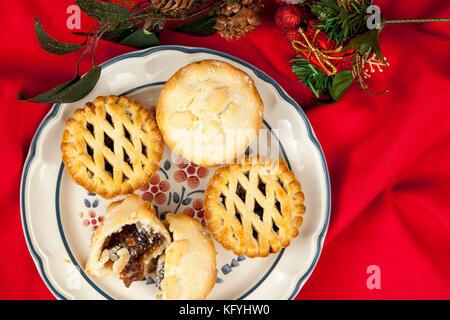 Vergoldete Gitter oben Torten zu Weihnachten auf einem Rüschen rot Tischdecke mince mit einigen festlichen saisonale - Stockfoto