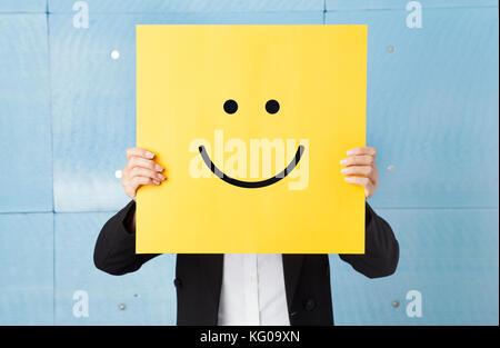Junge Frau ihr Gesicht verstecken mit einem gelben Papier mit einem Smiley auf es - Stockfoto