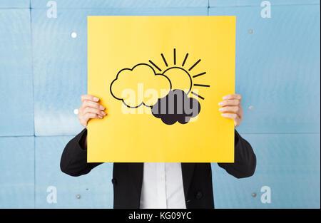 Junge Frau ihr Gesicht verstecken mit einem gelben Papier mit Wolken und Sonne auf sie - Stockfoto