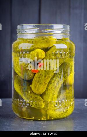 Eingelegte Gurken oder Gurken im Glas auf einem grauen Hintergrund. - Stockfoto