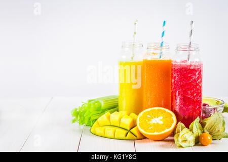 Mehrfarbige Smoothies in Flaschen von Mango, Orange, Banane, Sellerie, Beeren, auf einem Holztisch - Stockfoto