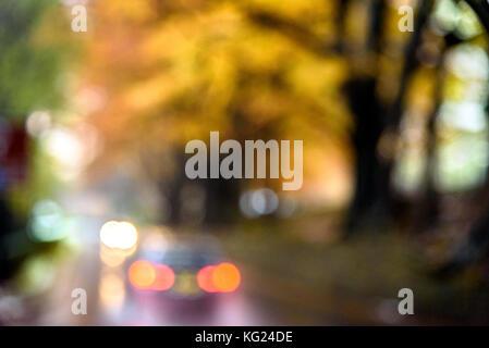Abstraktes Bild von Auto Licht bokeh gegen die bunten Bäume im Herbst. - Stockfoto