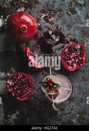 Alkoholfreien cocktail garniert mit Granatapfel Samen auf dunklen Moody Hintergrund - Stockfoto