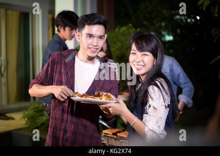 Asiatisches junges Paar beim romantischen Dinner und eine Gruppe von Freunden in Außenbereich Garten Grill Lachen - Stockfoto