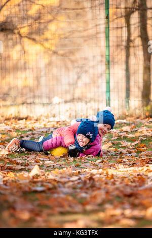 Die beiden kleinen Mädchen spielen im Herbst Blätter - Stockfoto