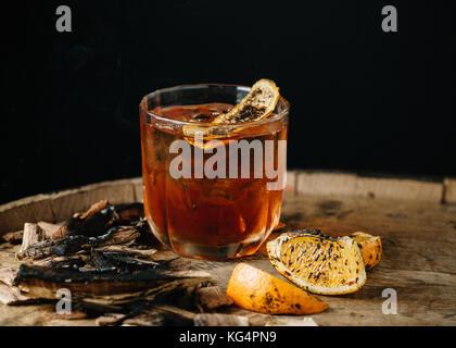 Geräucherter altmodische Cocktail garniert mit einer Orangenhaut auf dunklem Hintergrund - Stockfoto