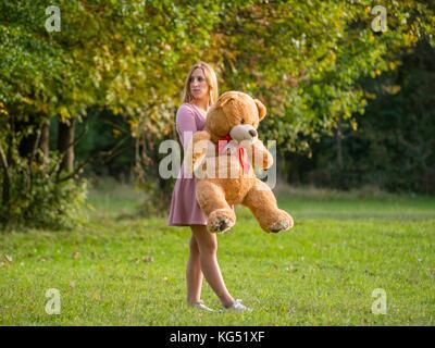 Angepirscht jugendlich Mädchen mit Teddy auf der grünen Wiese - Stockfoto